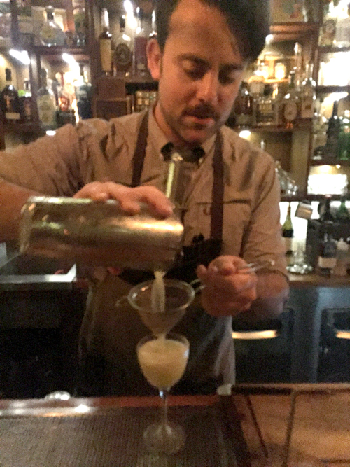 The bartender at The Attic prepares a Tequila and Mezcal based cocktail